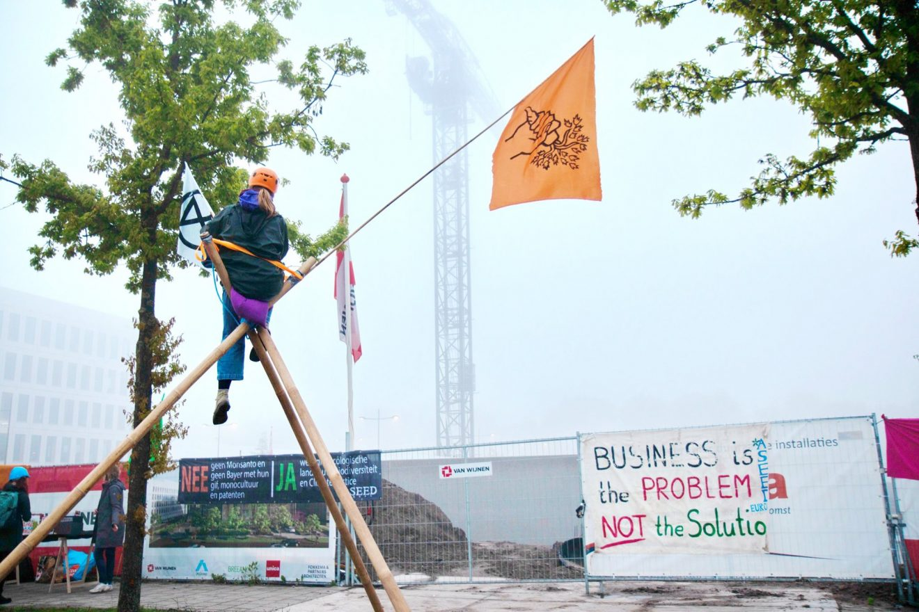 A person in a tripod in front of the Unileper Construction site. Banners are on the construction fences